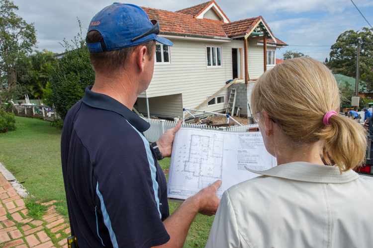 Home Builder Jason Mangan Showing House Plans To Home Owner