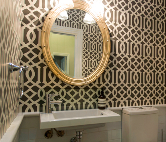 Bold Patterned Wallpaper Bathroom With Gold Framed Oval Mirror And Half White Tiled Wall