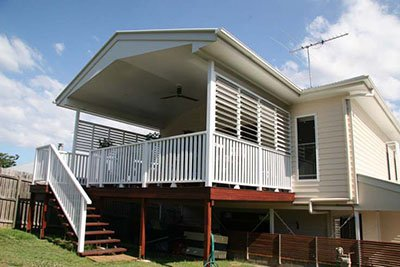 Queenslander House Renovation With White Deck Fencing And Burnt Red Wood Finish To The Supporting Beams and Pillars