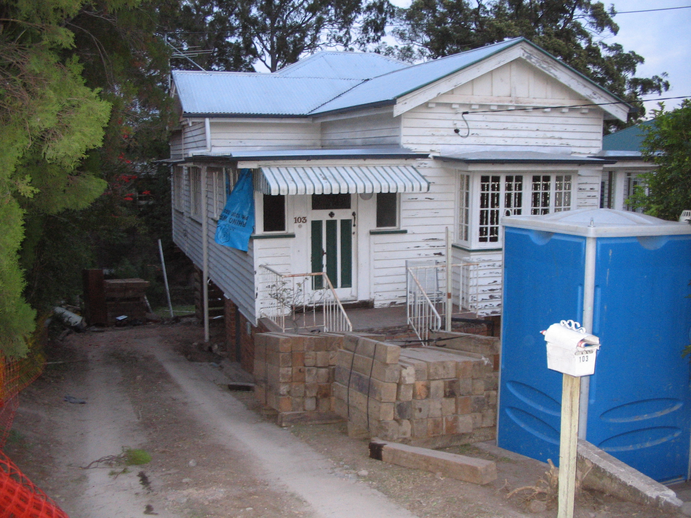 Old And Rundown Queenslander With Peeling White Paint And Untidy Exterior And Garden